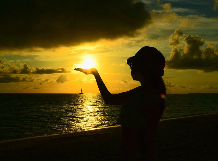 Optical illusion of silhouette woman holding sun at beach against sky during sunset