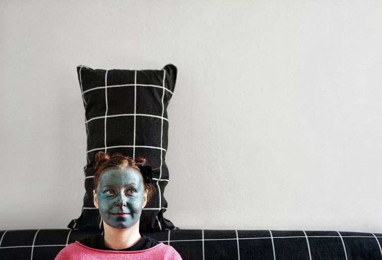 Close-up of woman with facial mask sitting against wall