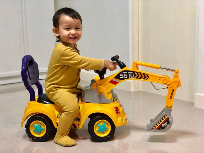 Toddler boy sitting on a digger toy One Person Mixed Race Childhood Child Boys Full Length Males  One Person Casual Clothing Men Car Yellow Real People Toy Car Innocence Happiness Lifestyles