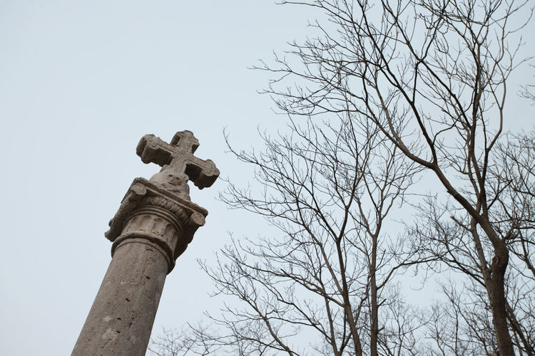 Low angle view of cross on tree against sky