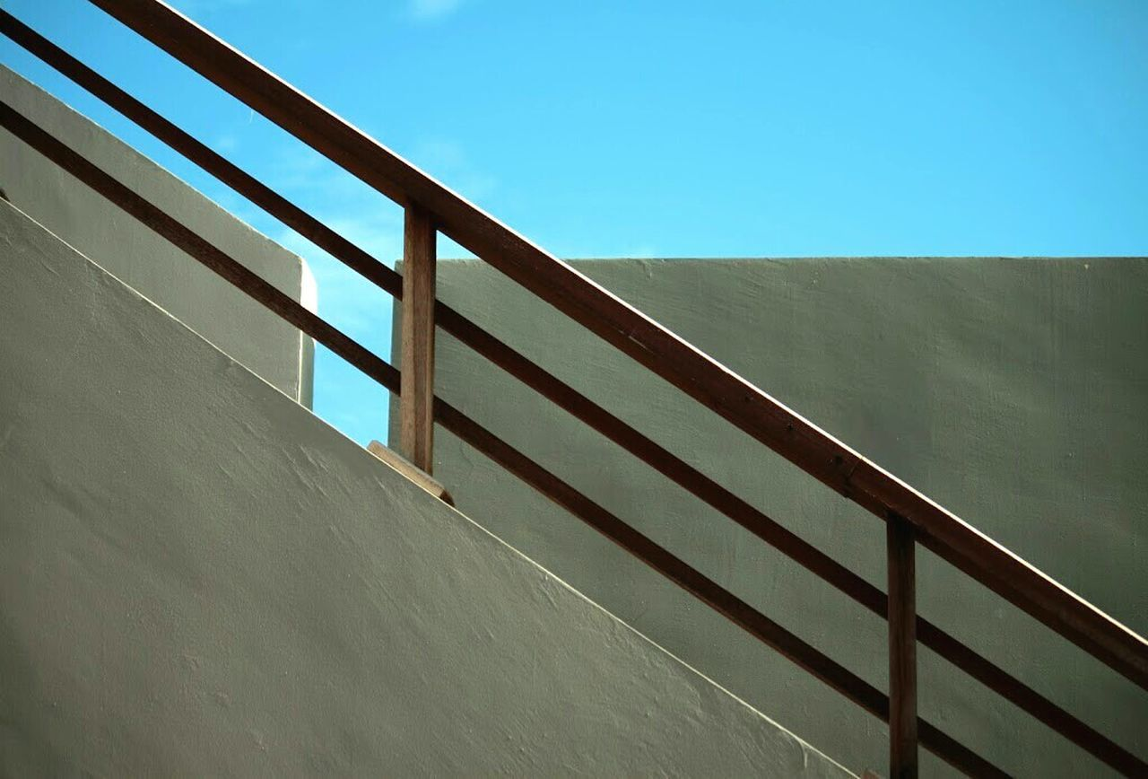 Low Angle View Of Railing By Wall Against Clear Blue Sky