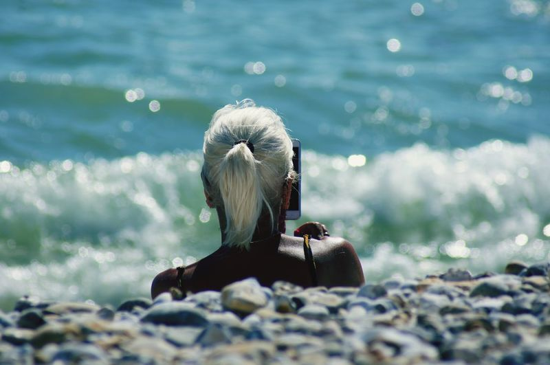 A white haired woman over the vanishing point facing towards the sea. Beauty In Nature Beach Land Outdoors Suntanned Hairstyle Hair Human Head Human Body Part White Hair Adult Mature Women Real People One Person Multi Colored Pebble Beach Motion Wave Sea Reflection Silhouette Sunlight vanishing point EyeEm Selects Water Day Nature Close-up Selective Focus Focus On Foreground