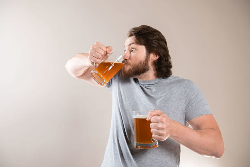Man drinking glass on table against white background