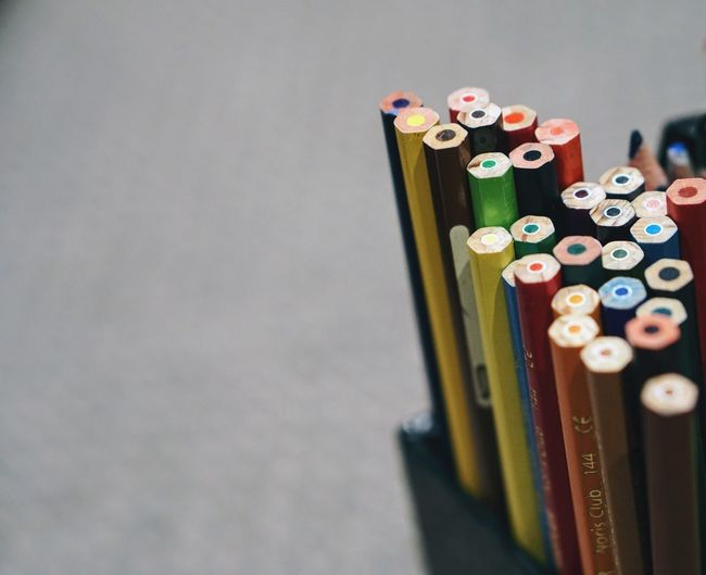 Close-up of colored pencils in desk organizer on table