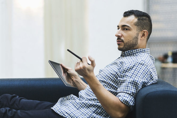 Midsection of man using mobile phone while sitting on sofa