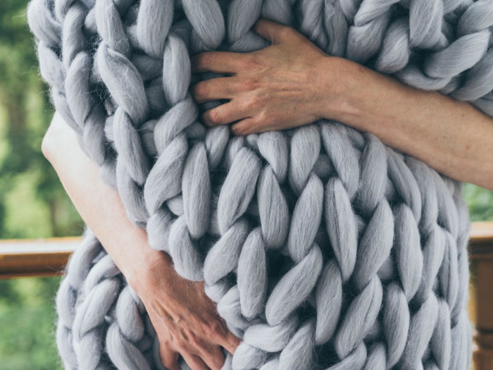 Midsection Of Woman Embracing Rug