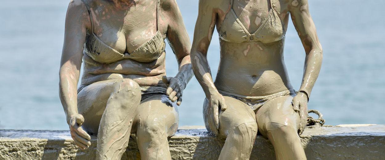 Midsection of muddy women wearing bikini while sitting at beach