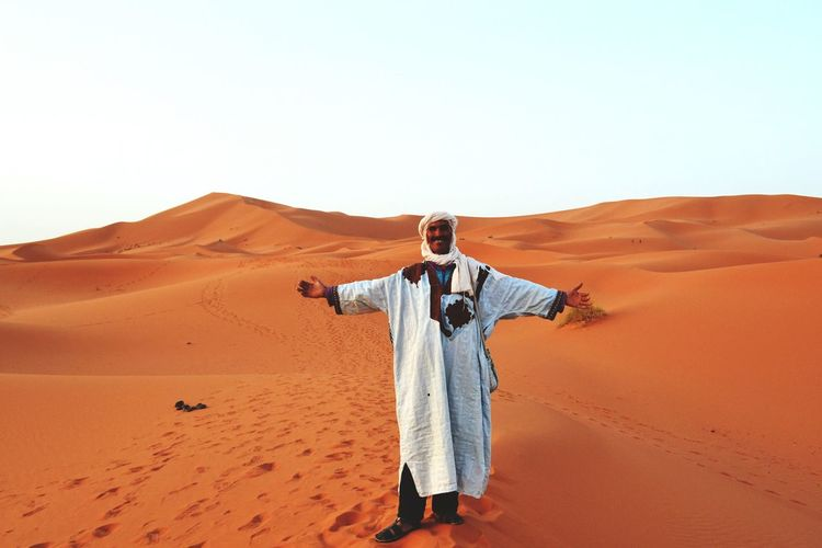 Full length of man with arms outstretched standing at desert against clear sky