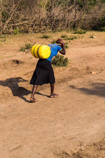 Woman Carrying Container While Walking On Dirt Road