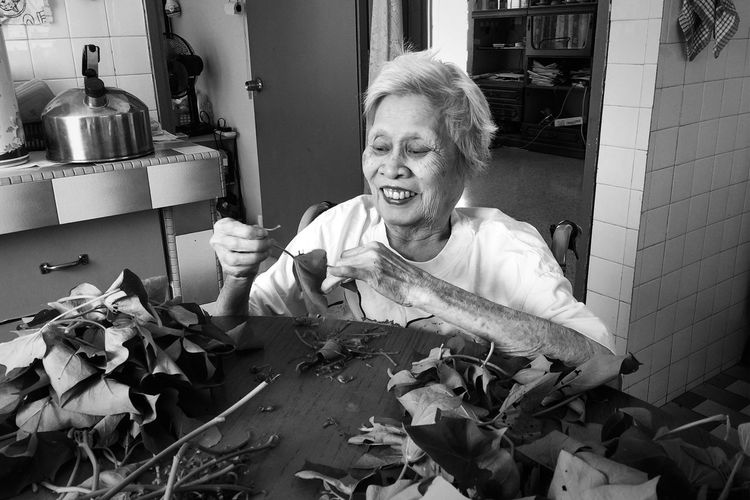 Senior woman holding dried leaf at table