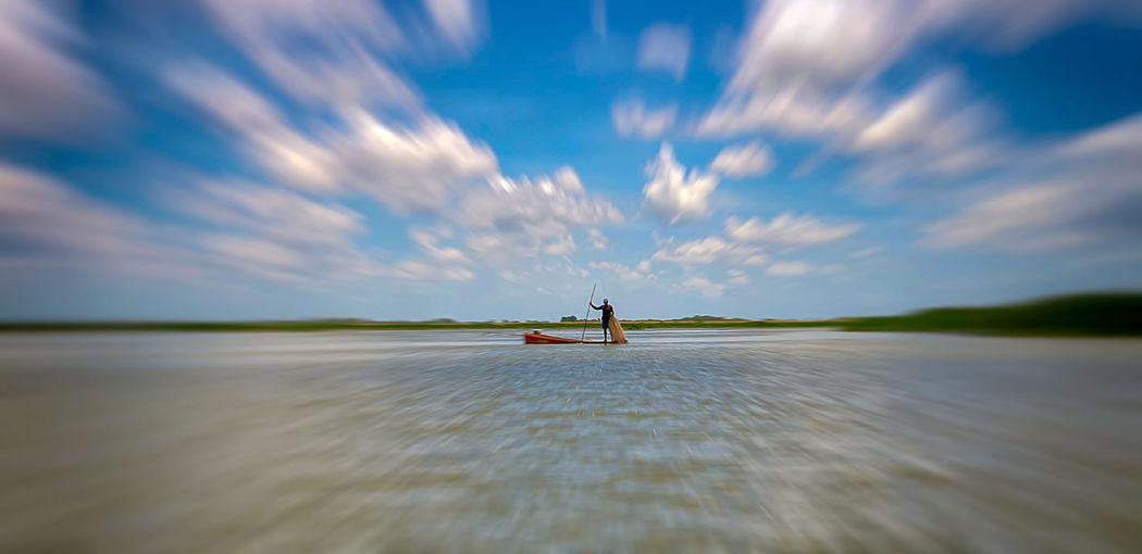 Fisherman On Wooden Boat Sky Cloud - Sky Water Scenics - Nature Nature Long Exposure Beauty In Nature Environment Motion Landscape Blurred Motion Horizon Transportation Travel Tranquil Scene Tranquility Day Outdoors Fishing Fishing Boat Fisherman