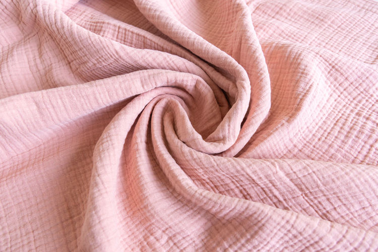 Soft muslin baby blanket. cotton and textiles. natural organic fabrics texture. light pink color.