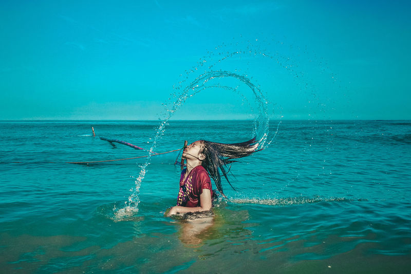 Side view of woman tossing hair in sea against blue sky