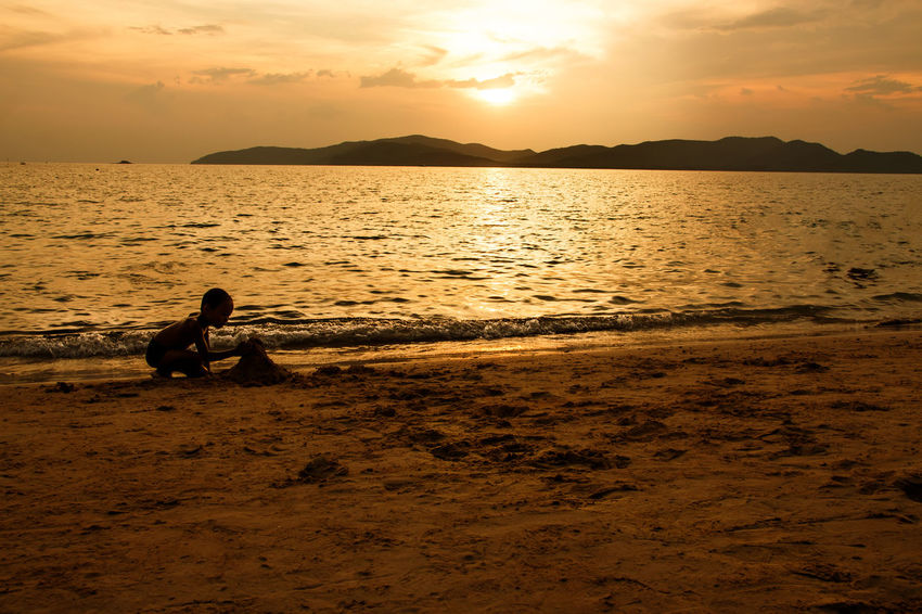 silhouette of people at the beach,The beauty of natural light at sunset. Sunset Sky Real People Water Beauty In Nature Men Sitting Scenics - Nature Sea Lifestyles Leisure Activity Beach Two People Silhouette Land Cloud - Sky Orange Color Nature Tranquil Scene Outdoors Couple - Relationship Silhouette Happiness Happy People Holiday Relaxing Children Women Man Romantic Orange Clouds And Sky Love Family Summer Sunrise Boy Freshair Freedom Fun