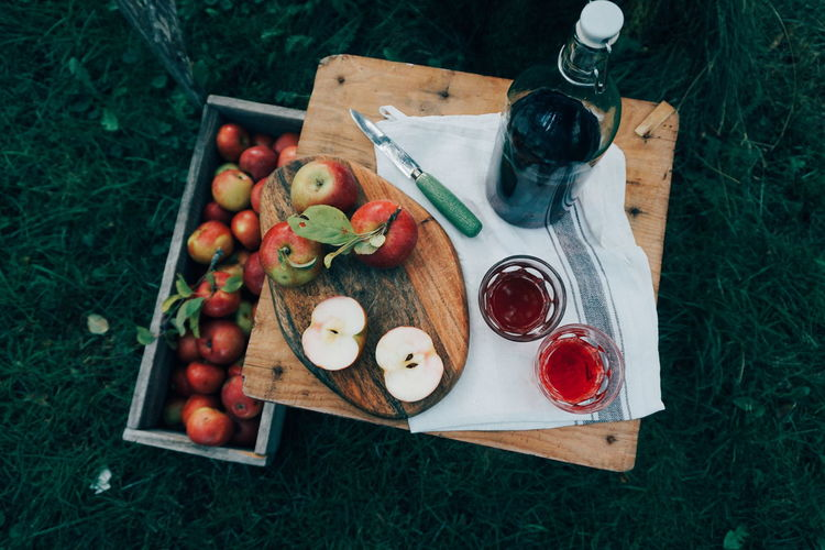 High angle view of apples with drink on wooden table in farm