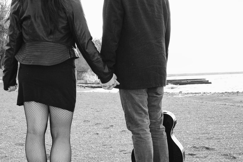 Midsection of man with guitar holding woman hand on beach
