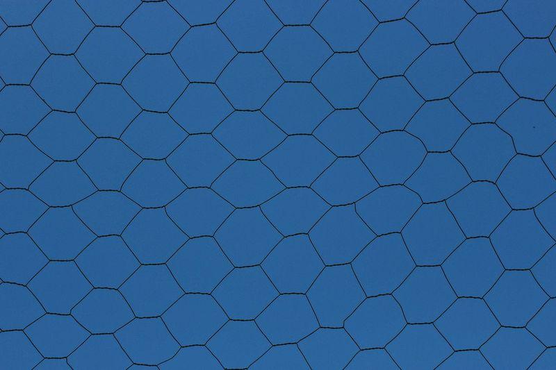 Full frame shot of chainlink fence against blue sky