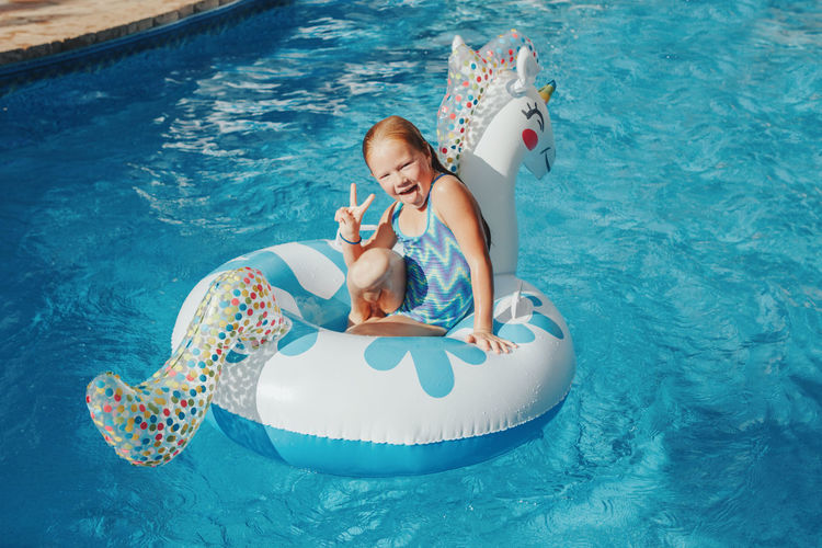 Smiling caucasian girl lying on inflatable ring unicorn. kid child having fun in swimming pool