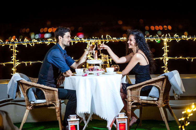 Couple Toasting Drinks On Illuminated Terrace At Night