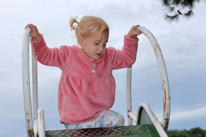 Cute girl on slide against sky at playground