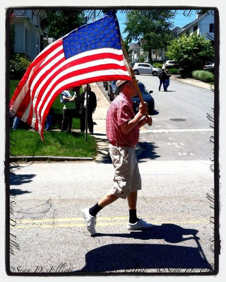 Boy Scout leader carries the flag.