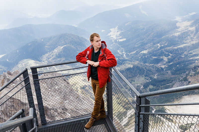 Portrait of man standing on railing against mountains