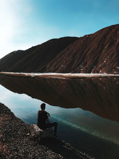 Man sitting at lakeshore by mountains against sky