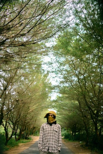Rear view of man standing on road amidst trees in forest