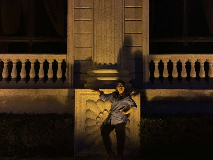 Woman standing by architectural column against concrete fence at night