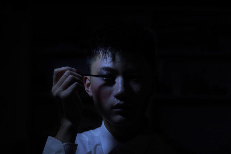 Man Applying Mascara In Darkroom