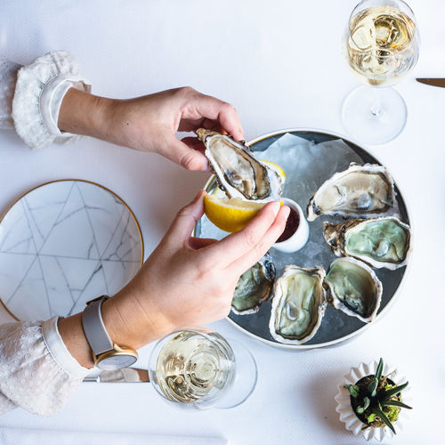 One Person Hand Human Hand Food And Drink Real People Holding Food Seafood Lifestyles Indoors  Table Glass Freshness Healthy Eating Shell Household Equipment Drink Human Body Part High Angle View Oyster  White Background