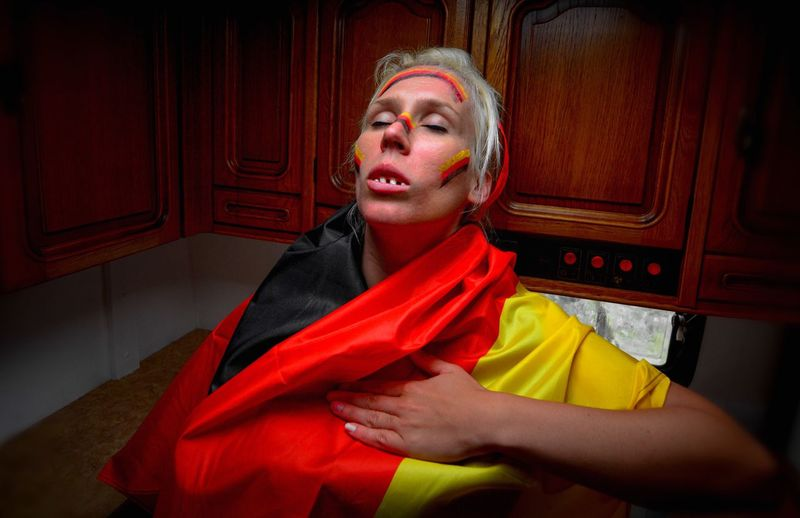 Woman With German Flag And Face Paint At Home