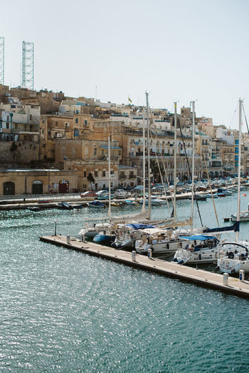 Boats moored in harbor by buildings against clear sky