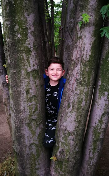 Portrait of smiling boy standing by tree in forest