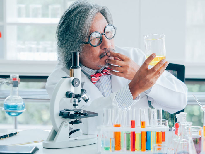 Science Education Healthcare And Medicine Laboratory Research Eyeglasses  Scientific Experiment Glasses Occupation Indoors  One Person Laboratory Equipment Scientist Real People Adult Mature Adult Front View Looking Analyzing Optical Instrument Lab Coat Microscope Medical Research Biology Test Tube Rack