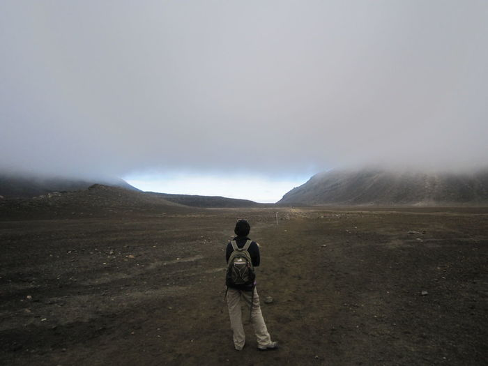 Rear view of backpack woman standing on field against cloudy sky