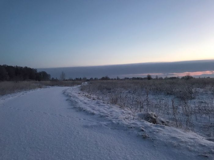 Snow covered land against clear sky during sunset