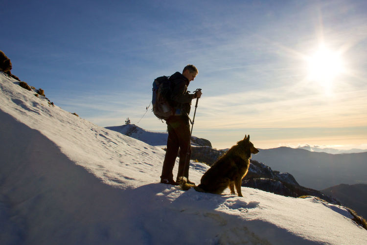 Man with dog standing on snow against sky