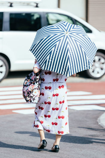 Rear view of woman with umbrella walking on street