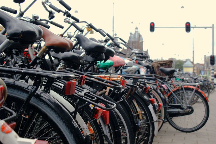 Transportation Mode Of Transportation Land Vehicle Bicycle Stationary City Focus On Foreground Parking Lot Day Parking Street No People Outdoors Wheel Architecture Motorcycle In A Row Close-up Large Group Of Objects Bicycle Rack Spoke Pollution Cloudy Day It's About The Journey 2018 In One Photograph The Traveler - 2019 EyeEm Awards