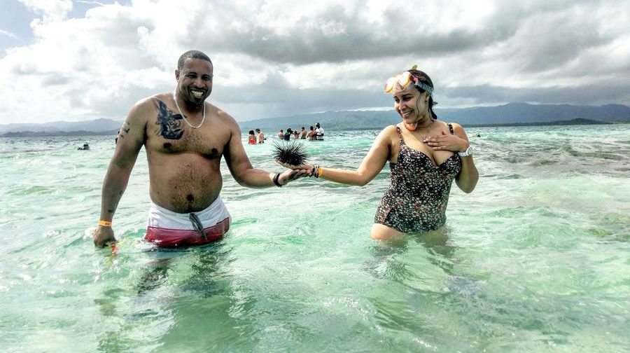 Portrait of smiling couple holding sea urchin while standing in sea against sky