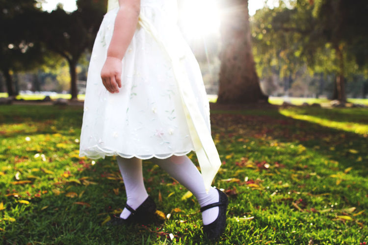 Low section of girl walking on grass in park