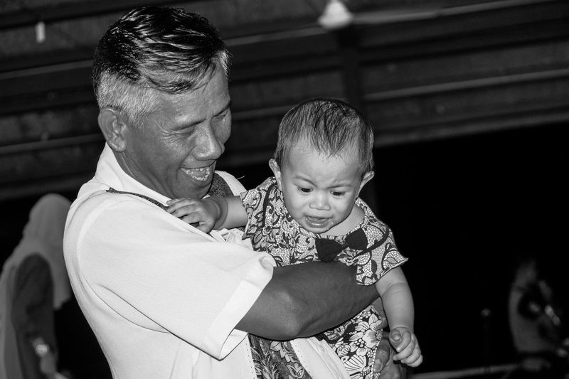 Close-Up Of Happy Grandfather Carrying Crying Granddaughter
