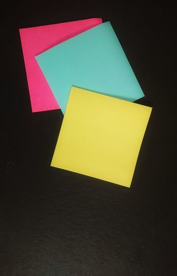 High angle view of yellow paper against black background
