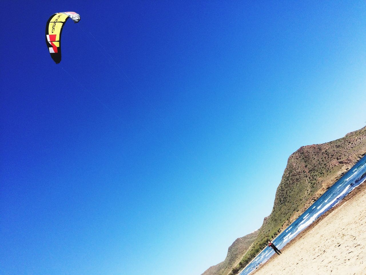 copy space, blue, clear sky, day, adventure, low angle view, outdoors, mountain, no people, nature, beauty in nature, parachute, sky, paragliding
