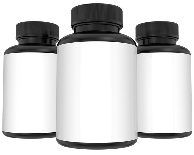 Close-up of pill bottles against white background