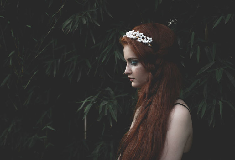 Profile view of young woman wearing tiara against plants