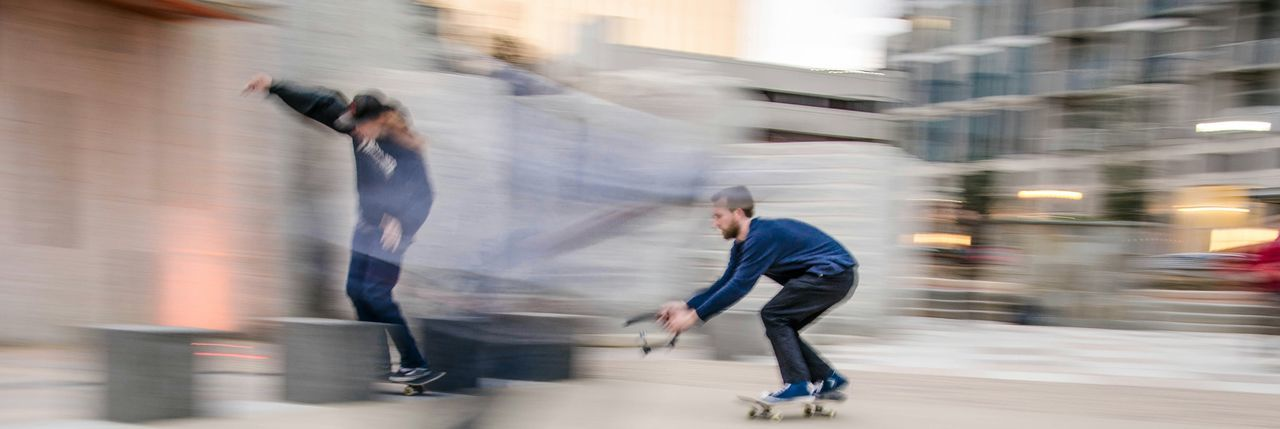 Full length side view of two men skateboarding