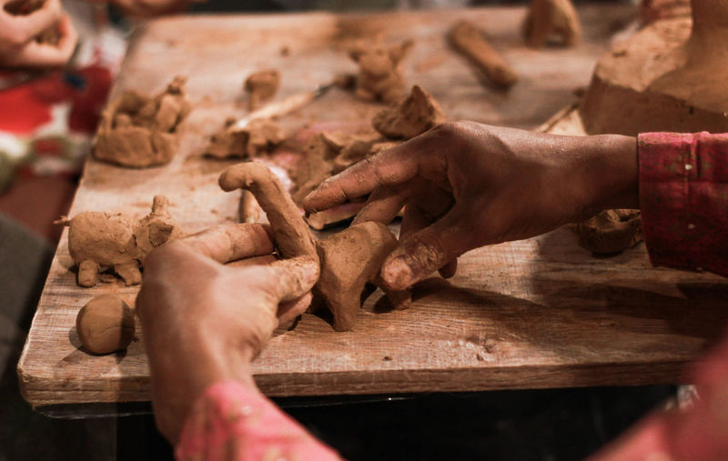 Cropped hands making clay toys on table