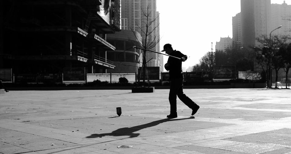 Side View Of Silhouette Man Playing On Footpath